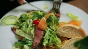Kvinna som äter sallad i restaurangen, steadycamskott stock video