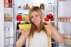 Kvinna som äter sallad nära kylskåpet Royaltyfria Bilder