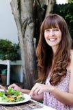 Kvinna som äter sallad som äter middag alfresco arkivfoto