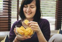 Kvinna som äter sjuklig mat bara arkivbilder