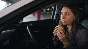 Kvinna som äter smörgåsen som sitter i bilen på parkeringen Begrepp av ett modernt upptaget liv lager videofilmer