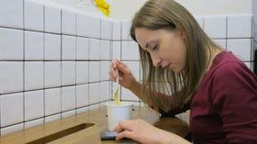 Kvinna som äter soppa och använder smartphonen i kafé Royaltyfri Foto