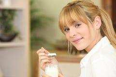 Kvinna som äter yoghurt Arkivbild
