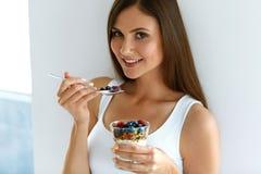Kvinna som äter yoghurt, bär och havremjölet för sund frukost arkivbilder