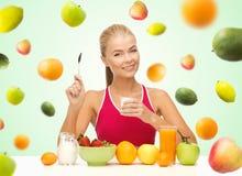 Kvinna som äter yoghurt och har den sunda frukosten Royaltyfri Fotografi
