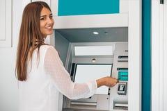 Kvinna som återtar pengar från ATM-maskinen royaltyfria bilder