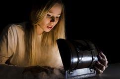 Kvinna som öppnar en liten bröstkorg med en rök som kommer ut ur den Arkivfoton