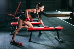Kvinna som övar hantelrad på idrottshallen Royaltyfria Bilder