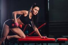 Kvinna som övar hantelrad på idrottshallen Royaltyfri Fotografi