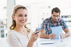 Kvinna som överför ett textmeddelande med hennes kollega bakom Arkivfoton