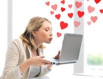 Kvinna som överför kyssar med bärbar datordatoren Fotografering för Bildbyråer