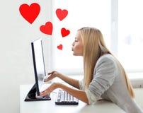 Kvinna som överför kyssar med datorbildskärmen Arkivbilder