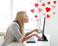 Kvinna som överför kyssar med datorbildskärmen Royaltyfri Bild
