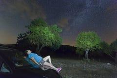 Kvinna som överst ligger av en nattbil i stjärnljuset Arkivbild