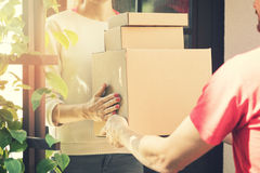 Kvinna som accepterar en hem- leverans av askar från bud Royaltyfria Foton