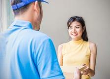 Kvinna som accepterar en leverans av askar från bud Fotografering för Bildbyråer