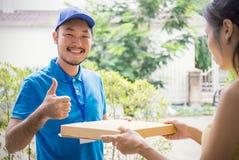 Kvinna som accepterar en leverans av pizzaasken Arkivfoton