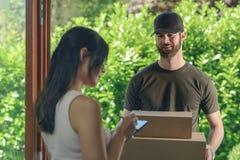 Kvinna som accepterar en leverans av två kartonger Arkivbild