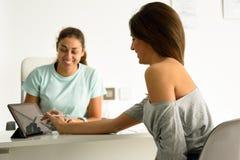 Kvinna som accepterar och undertecknar hennes diagnos med kvinnlig physiother Arkivbilder