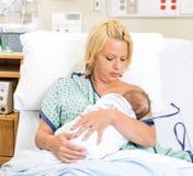 Kvinna som ammar nyfödda Babygirl i sjukhus Arkivbilder