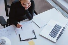 Kvinna som analyserar diagrammet av framsteg och att planera för arbete royaltyfria foton