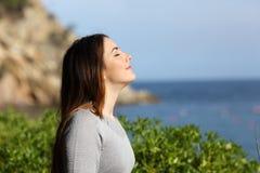 Kvinna som andas ny luft som kopplas av på semester arkivbilder