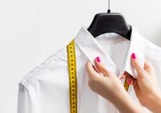 Kvinna som anpassar affärsskjortan Fotografering för Bildbyråer