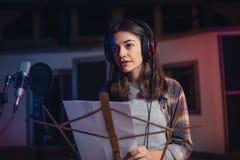 Kvinna som antecknar en sång i musikstudio Royaltyfri Foto