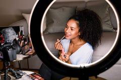 Kvinna som antecknar makeup som är orubblig med dslr arkivfoto