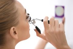 Kvinna som använder ögonfranshårrullen arkivfoto