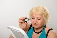 Kvinna som använder ögonfranshårrullen. Royaltyfria Bilder