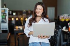 Kvinna som använder bärbar datordatoren i kafé Royaltyfri Bild