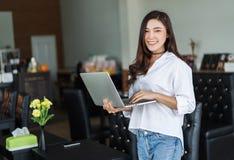 Kvinna som använder bärbar datordatoren i kafé Royaltyfri Foto