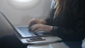 Kvinna som använder bärbara datorn eller persondatorn som sitter i flygplan arkivfilmer