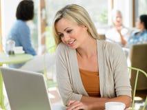 Kvinna som använder bärbara datorn i kafé Royaltyfri Foto