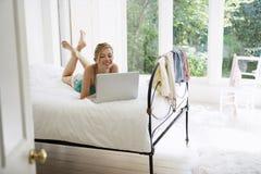 Kvinna som använder bärbara datorn i säng Royaltyfria Bilder