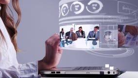 Kvinna som använder bärbara datorn med affärshologrammanöverenheten lager videofilmer