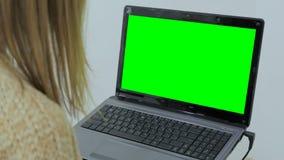 Kvinna som använder bärbara datorn med den gröna skärmen Arkivfoto