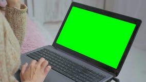 Kvinna som använder bärbara datorn med den gröna skärmen Fotografering för Bildbyråer