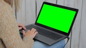 Kvinna som använder bärbara datorn med den gröna skärmen Royaltyfri Bild