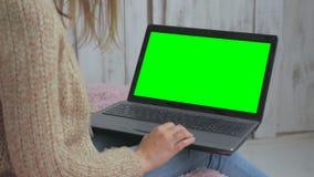 Kvinna som använder bärbara datorn med den gröna skärmen Arkivbild