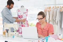 Kvinna som använder bärbara datorn med modeformgivaren som arbetar på studion Arkivfoto