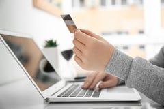 Kvinna som använder bärbara datorn, medan rymma kreditkorten Arkivfoton