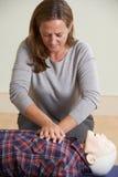 Kvinna som använder CPR-teknik på attrapp i första hjälpengrupp Arkivfoton