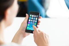 Kvinna som använder den Apple iPhonen 5S Royaltyfri Foto