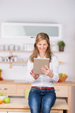 Kvinna som använder den Digital minnestavlan i kök Arkivbilder