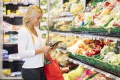 Kvinna som använder den Digital minnestavlan i livsmedelsbutik royaltyfria bilder