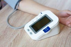 Kvinna som använder den digitala blodtryckbildskärmen Royaltyfri Foto