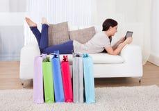Kvinna som använder den digitala minnestavlan med shoppingpåsar på golv arkivbild