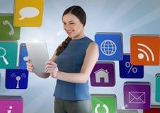 Kvinna som använder den digitala minnestavlan mot digitalt frambragda datorsymboler Arkivfoton